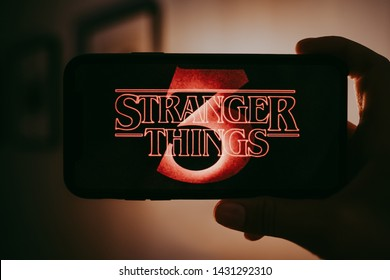 ROSTOV-ON-DON / RUSSIA - June 22 2019: Stranger Things 3 from Netflix TV series Poster, hands holding the iPhone with shot of Stranger Things Season 3