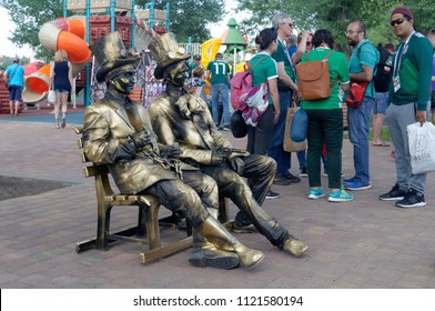 "Rostov-on-Don, Russia - June 23, 2018: Living sculpture of two people on the bench. Embankment near the football stadium ""Rostov Arena"""