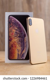Rostov-on-Don, Russia - November 2018.  Apple iPhone XS Max 6.5-inch display and box on a wooden surface. Golden color iPhone XS Max box and smartphone on wooden table.