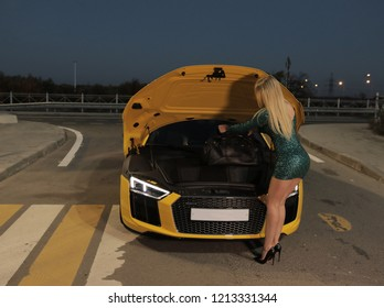 Rostov-on-Don, Russia - October 19, 2018. Girl puts her bag in Audi R8 front trunk