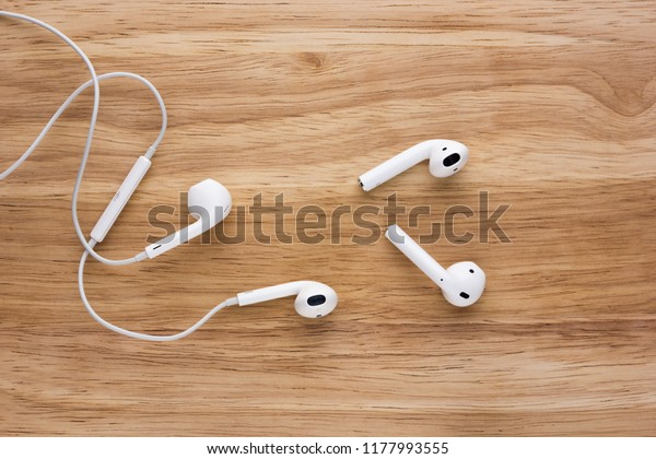 Rostov-on-Don, Russia - September 2018: Airpods and Earpods are lying on a wooden surface. Two pairs of headphones from apple on a wooden table.