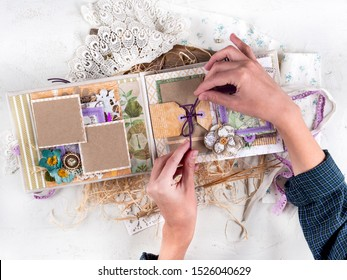Rostov-on-Don, Russia, September 2019. Scrapbooking handmade photo album. Diy. Top view on table with elements for scrapbooking, cut paper, die cuts, paper flowers, ribbons,embossing. Women's hobby.