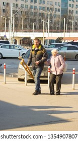 Rostov-on-don, Russian Federation, March 25, 2019. A lame old white woman of short stature accompanied by a white middle-aged man of tall stature holding two wooden crutches go from the car Park on th