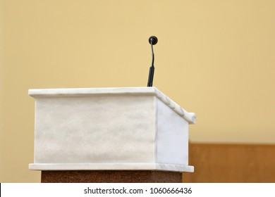 Rostrum with microphone in conference hall or church altar and empty space for text