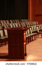 Rostrum with microphones and glass of water in empty auditorium. Prepared to business meeting