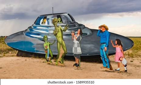 ROSWELL, NEW MEXICO - OCTOBER 8, 2019:  Roswell, New Mexico welcome sign cutouts with a alien and human family encounter, and a flying saucer spaceship.