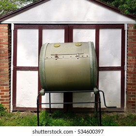 Rotary composting bin against shed.