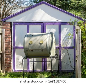 Rotary composting bin against white old fashioned garage with purple trim.