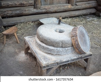 Rotary discoid mill stone for hand-grinding a grain into flour. Medieval hand-driven millstone grinding wheat. The ancient Quern stone hand mill with grain near log house or russian izba