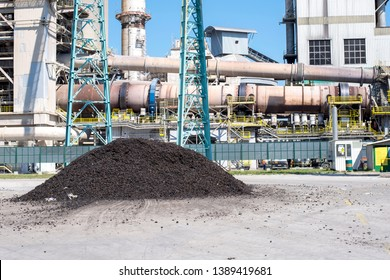 Rotary kiln in cement plant with shredded tires in foreground used as alternative fuel.