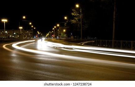 rotate cars at night, the traces of the headlights as lines of light, night city intersection the view from the level of the human eye