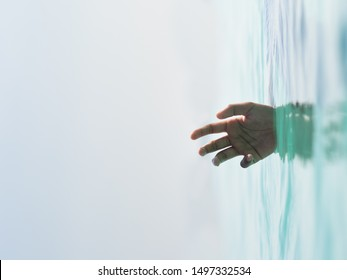 rotated image of a hand sinking in a water. concept of helpless, drown, loneliness