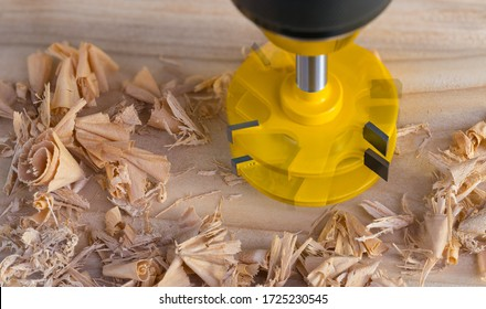 Rotating copying groove milling cutter on wooden plank with scattered curled shavings. Yellow shank router bit with precise sharp edges. Motion blur of turning cutting tool. Woodwork, wood technology.