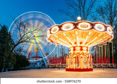 Rotating Illuminated Attraction Ferris Wheel And Carousel Merry-go-round On Summer Evening In City Amusement Park.