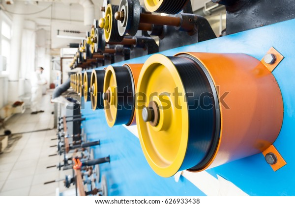 Rotating rubberized wheels of the winding machine. A lot of rotating wheels are yellow.