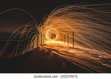 Rotating steel wool with sparkling burning sparks in the night with long exposure shutter photographed in different variations
