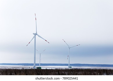 Rotating wind turbines in the distance in a snowy field in the background of a haze of a winter sky