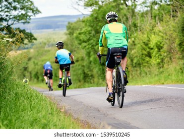 ROTHBURY, NEWCASTLE UPON TYNE, ENGLAND, UK - JULY 06, 2019: Three cyclists riding along a country lane at the cyclone race event from Newcastle to Northumberland.