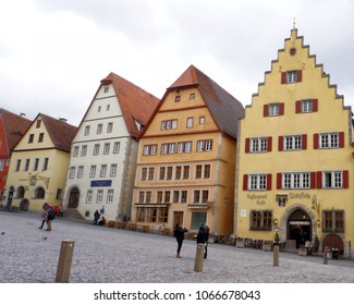 ROTHENBURG, BAVARIA / GERMANY - March 12, 2018: Unnamed tourists pause to take photos in the center of Rothenburg's town square.