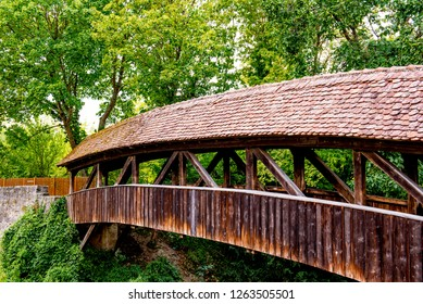 Rothenburg ob der Tauber, Bavaria, Germany - August 17 2018: A wooden covered bridge near the Spital Bastion at the south entrance to the old town of Rothenburg ob der Tauber.