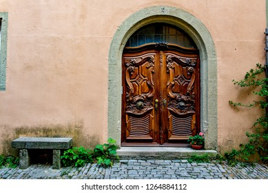 Rothenburg ob der Tauber, Bavaria, Germany - August 17 2018: Ornate wooden curved door on the cobblestoned streets of Rothenburg ob der Tauber, Germany