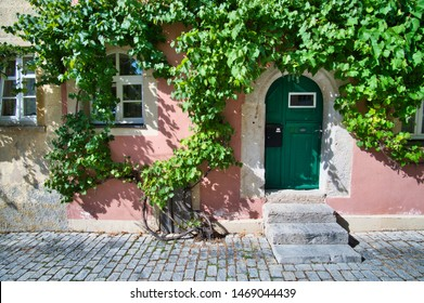 Rothenburg ob der Tauber, Bavaria / Germany - August 2, 2019: Lovely house entrance with winegrapes in the historic old town of Rothenburg ob der Tauber