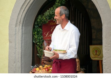 Rothenburg ob der Tauber, Bavaria/Germany 5/17/2018: A baker smiles as he offers tourists samples of his fresh baked goods.