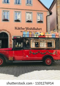 ROTHENBURG OB DER TAUBER, GER - MAY 6, 2018: Red polished advertising vintage car with Xmas parcels on its roof, belonging to Käthe Wohlfahrt museum. Traditional house background, cobblestoned alley.