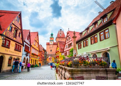 ROTHENBURG OB DER TAUBER, GERMANY, 17 JULY, 2017: Tourists walk along beautiful streets in Rothenburg ob der Tauber with traditional German houses, Bavaria, German