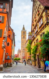 ROTHENBURG OB DER TAUBER, GERMANY, 17 JULY, 2017: Tourists walk along beautiful streets in Rothenburg ob der Tauber with traditional German houses, Bavaria, Germany