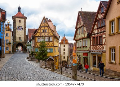 ROTHENBURG OB DER TAUBER, GERMANY -  DECEMBER 24, 2017: Tourists walk along beautiful streets in Rothenburg ob der Tauber with traditional German houses, Bavaria, Germany