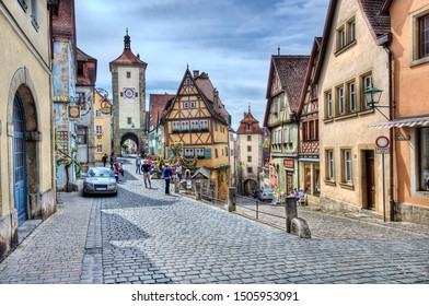 Rothenburg ob der Tauber, Germany - May 6, 2014: Historical street with people admiring the medieval architecture of houses and a clock tower gate in Rothenburg ob der Tauber, Germany on May 6, 2014.