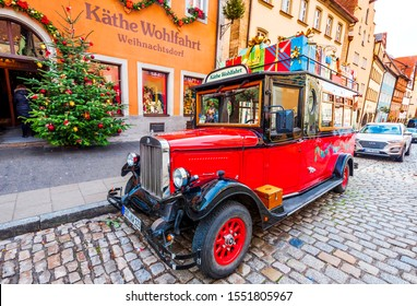 Rothenburg ob der Tauber, Germany - December 2018: Retro red car near a store selling traditional Christmas gifts in medieval old town in Bavaria