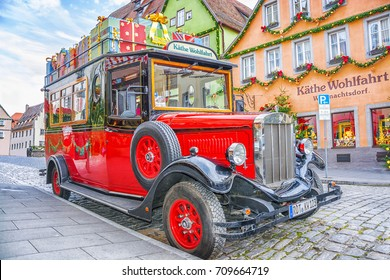 ROTHENBURG OB DER TAUBER, GERMANY - December 13, 2016: Retro red car with gift boxes near a store selling traditional Christmas gifts and Christmas toys on  street in medieval old town in Bavaria