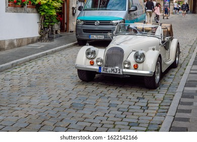 Rothenburg ob der Tauber\Germany-Aug 6, 2019 A classic car from the British  manufacturer Morgan moves along a  stone paved street in the medieval town of Rothenburg ob der Tauber.