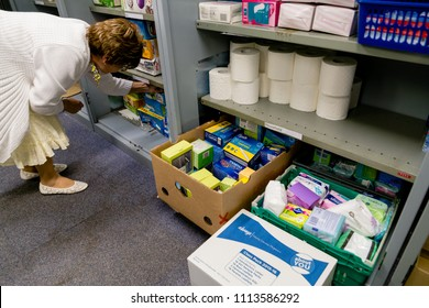 ROTHERHAM, ENGLAND - MAY 31, 2018: A local church food bank (part of Trussell Trust) dealing with period poverty - a female volunteer sorts products adjacent to a selection of sanitary products