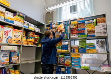 ROTHERHAM, ENGLAND - MAY 31, 2018: A local church food bank worker (Trussell Trust) organises cereal food stores & donations ready to give out parcels to clients in need.