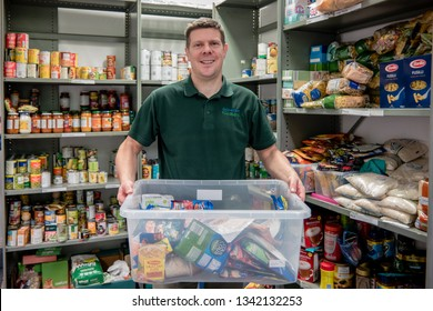 ROTHERHAM, ENGLAND, UK - FEBRUARY 14, 2019: A smiling volunteer man working at a Trussell Trust local church food bank holds donations in front of storage shelves