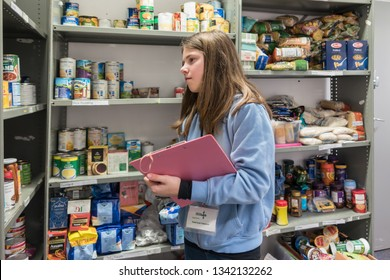 ROTHERHAM, ENGLAND, UK - FEBRUARY 14, 2019: A young female volunteer working at a Trussell Trust local church food bank stands in a foodbank warehouse with a clipboard and parcel packing sheet
