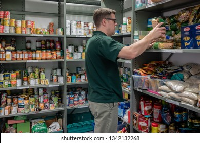 ROTHERHAM, ENGLAND, UK - FEBRUARY 14, 2019: A volunteer man working at a Trussell Trust local church food bank organises donations on shelves