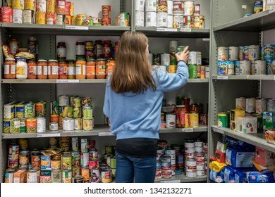ROTHERHAM, ENGLAND, UK - FEBRUARY 14, 2019: A young female volunteer working at a local church food bank (Trussell Trust) organises tins and donations ready to give out parcels to clients in need.