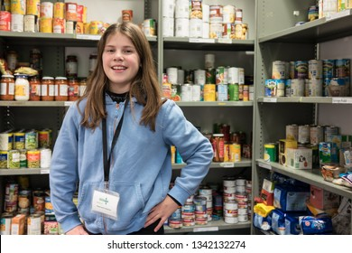 ROTHERHAM, ENGLAND, UK - FEBRUARY 14, 2019: A young female volunteer working at a Trussell Trust local church food bank stands smiling in front of food donations ready to give out parcels to clients