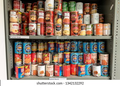 ROTHERHAM, ENGLAND, UK – FEBRUARY 14, 2019: Storage shelves in a Trussell Trust local church food bank warehouse showing tins of baked beans and soup ready for food parcels