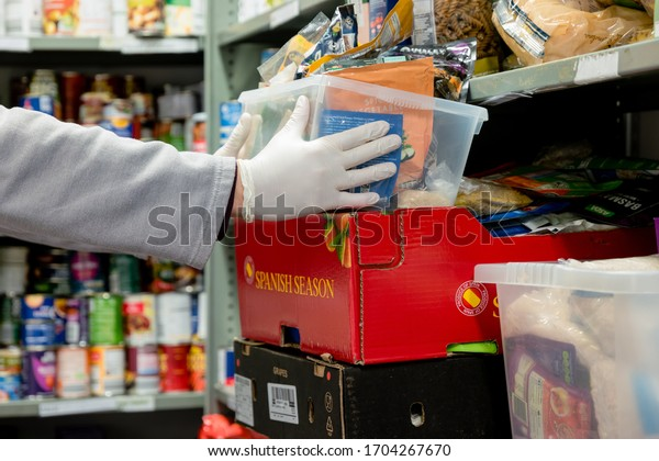 ROTHERHAM, UK - APRIL 14, 2020: A volunteer at a Trussell Trust food bank wears gloves PPE in the coronovirus pandemic whilst packing a client parcel