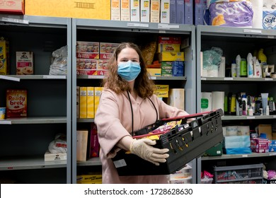 ROTHERHAM, UK - MAY 6, 2020: A volunteer at a Trussell Trust food bank wears gloves and face mask PPE in the coronovirus pandemic whilst packing a client parcel