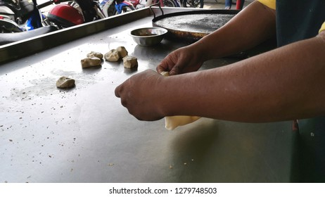 Roti canai or roti cane making process closeup with selective focus. It is a flatbread found in Malaysia, Brunei, Indonesia and Singapore. Roti Canai is very much loved by Malaysians.