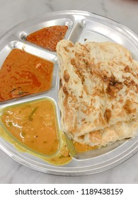 Roti canai, served with dal and curry. It is also known as roti cane or roti prata, an Indian-influenced flatbread dish found in several countries in Asia.