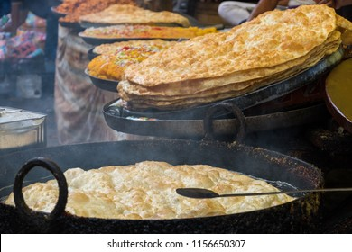 Roti fried on a frying pan. Street food Food of India. Making of Roti Canai,cooking process.Its also known as roti cane,is an Indian influenced flatbread dish found in several countries in Asia.