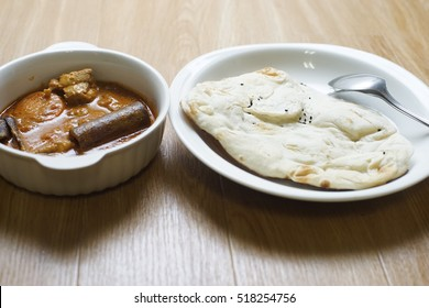 Roti nan with chicken curry over wooden background.