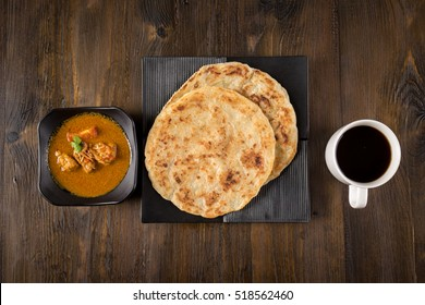 Roti Parata or Roti canai with chicken curry sauce and a cup of coffee, popular Malaysian breakfast.